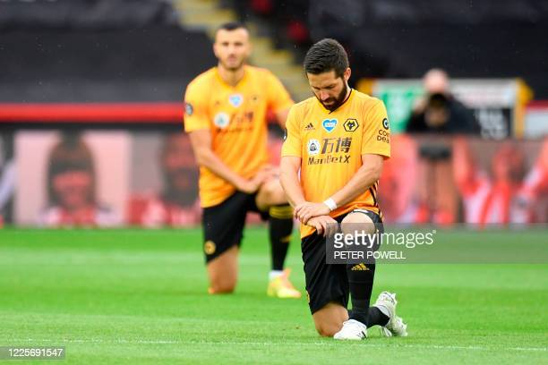 Wolverhampton Wanderers' Portuguese midfielder Joao Moutinho takes a knee in support of the Black Lives Matter movement at the start of the English...