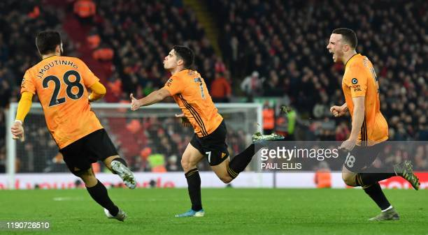 Wolverhampton Wanderers' Portuguese midfielder Pedro Neto celebrates with team-mates after putting the ball in the Liverpool net, a goal that was...