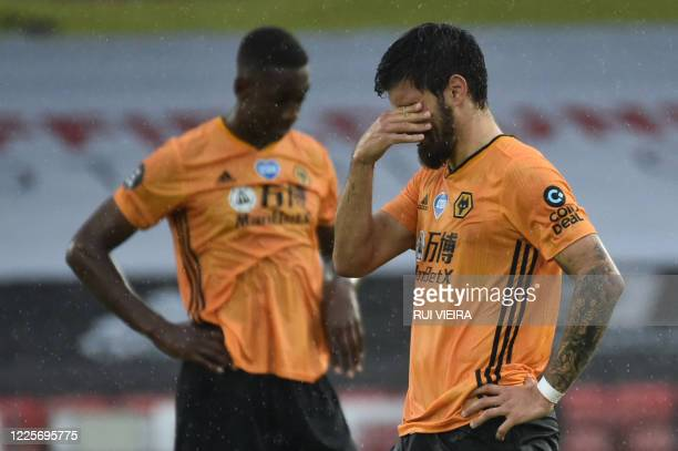 Wolverhampton Wanderers' Portuguese midfielder Ruben Neves and Wolverhampton Wanderers' French defender Willy Boly react at the end of the English...