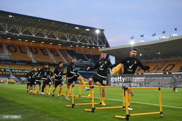 Wolverhampton Wanderers' Portuguese midfielder Ruben Neves and teammates warm up ahead of the English FA Cup fifth round football match between...