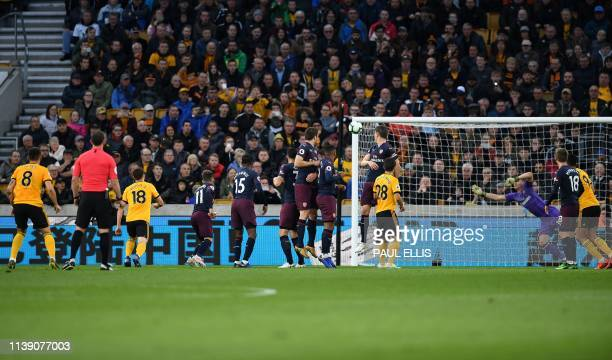 Wolverhampton Wanderers' Portuguese midfielder Ruben Neves watches the ball from his free kick as it goes into the net to score the opening goal...