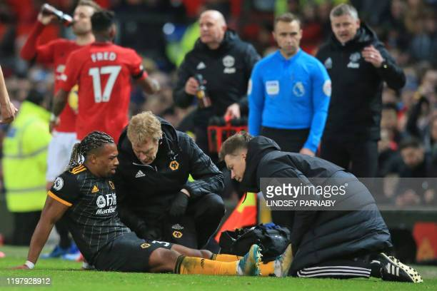 Wolverhampton Wanderers' Spanish midfielder Adama Traore receives medical attention after picking up an injury during the English Premier League...