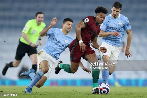 Wolverhampton Wanderers' Spanish midfielder Adama Traore runs past Manchester City's Portuguese defender Joao Cancelo and Manchester City's...