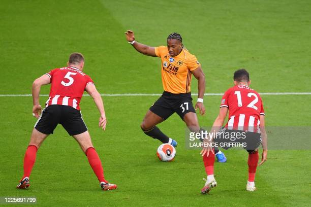 Wolverhampton Wanderers' Spanish midfielder Adama Traore vies with Sheffield United's English defender Jack O'Connell and Sheffield United's Irish...