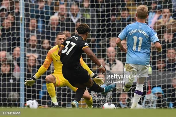 Wolverhampton Wanderers' Spanish striker Adama Traore scores the opening goal past Manchester City's Brazilian goalkeeper Ederson during the English...