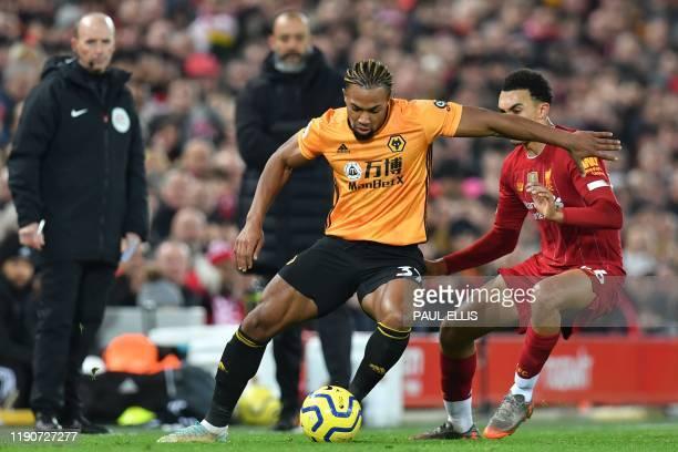 Wolverhampton Wanderers' Spanish striker Adama Traore takes on Liverpool's English defender Trent AlexanderArnold during the English Premier League...