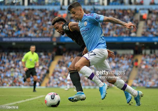 Wolverhampton Wanderers' Spanish striker Adama Traore vies with Manchester City's Portuguese defender Joao Cancelo during the English Premier League...