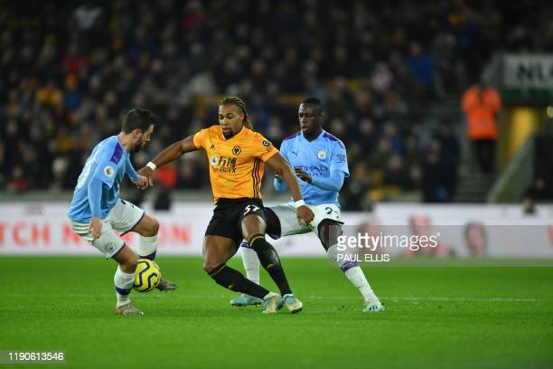 Wolverhampton Wanderers' Spanish striker Adama Traore vies with Manchester City's Portuguese midfielder Bernardo Silva and Manchester City's French...