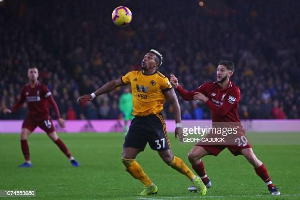 Wolverhampton Wanderers' Spanish striker Adama Traore vies with Liverpool's English midfielder Adam Lallana during the English Premier League...