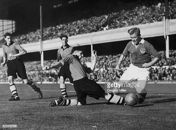 Wolves centre half Bill Shorthouse makes a sliding tackle on Portsmouth's Jack Froggatt during the FA Charity Shield match at Highbury Stadium,...