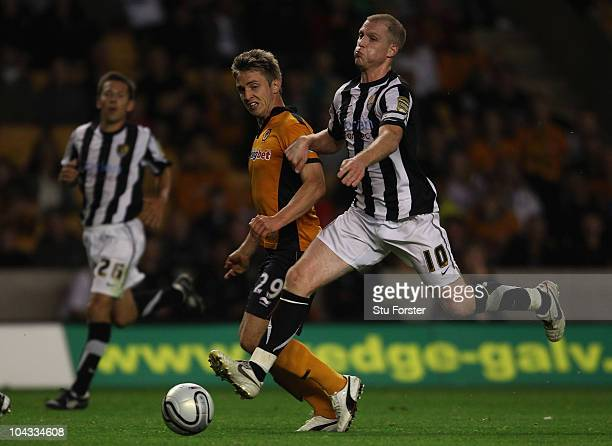 Wolves goalscorer Kevin Doyle shrugs off the challenge of Neal Bishop during the Carling Cup 3rd Round match between Wolverhampton Wanderers and...