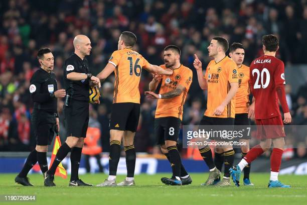 Wolves players argue with referee Anthony Taylor after their 1st goal was ruled out during the Premier League match between Liverpool FC and...
