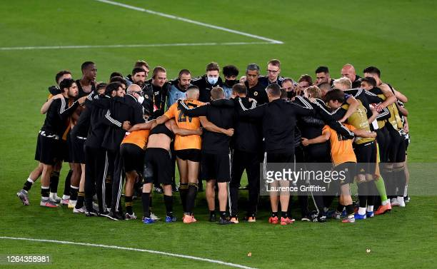 Wolves players gather to celebrate victory on the pitch after full-time during the UEFA Europa League round of 16 second leg match between...