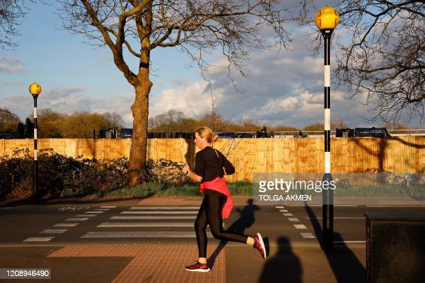 A wom jogs past a newly erected fence the boundary of a temporary mortuary during its construction in Manor Park east London on April 2 as part of...