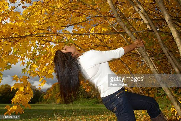 Womam pulling on tree in autumn