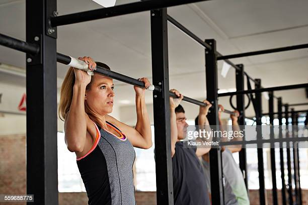 woman & 2 men doing pull-up's at gym gym - chin ups stock photos and pictures