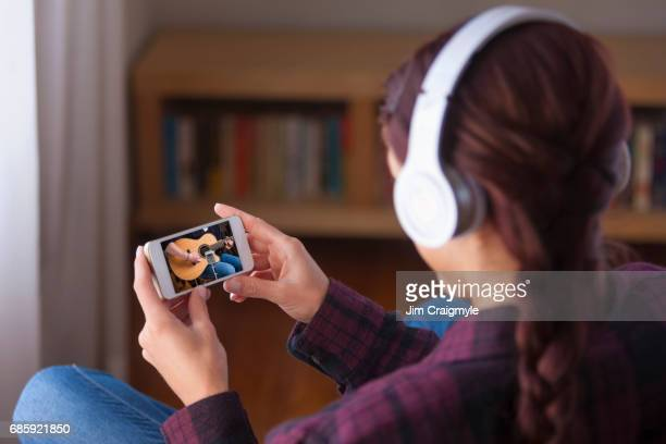 Woman 20's listening to music on a cell phone using wireless headphones
