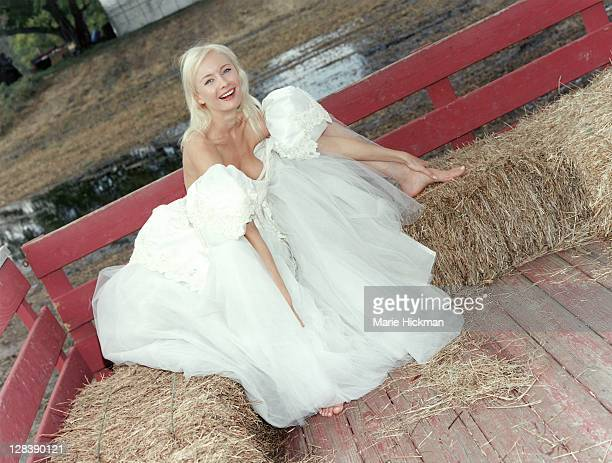 Woman, 24 years old, in wedding dress smiling sitting on haybales, Sherwood Farms, Easton, Connecticut