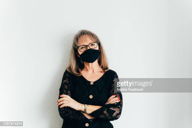 woman 50-55 years old wearing a black colored face mask and smiling with her eyes. - 55 59 years stock pictures, royalty-free photos & images