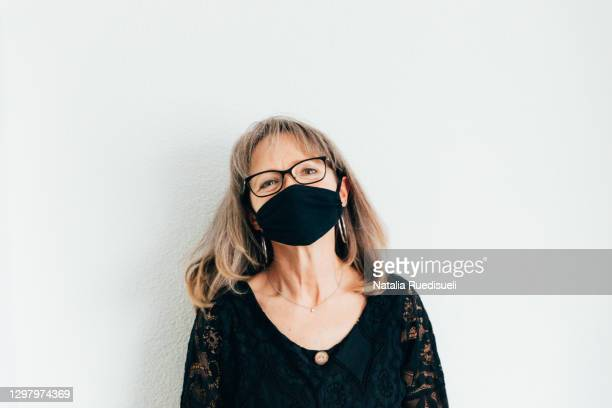 woman 50-55 years old wearing a black colored face protection and smiling. - 55 59 years stock pictures, royalty-free photos & images