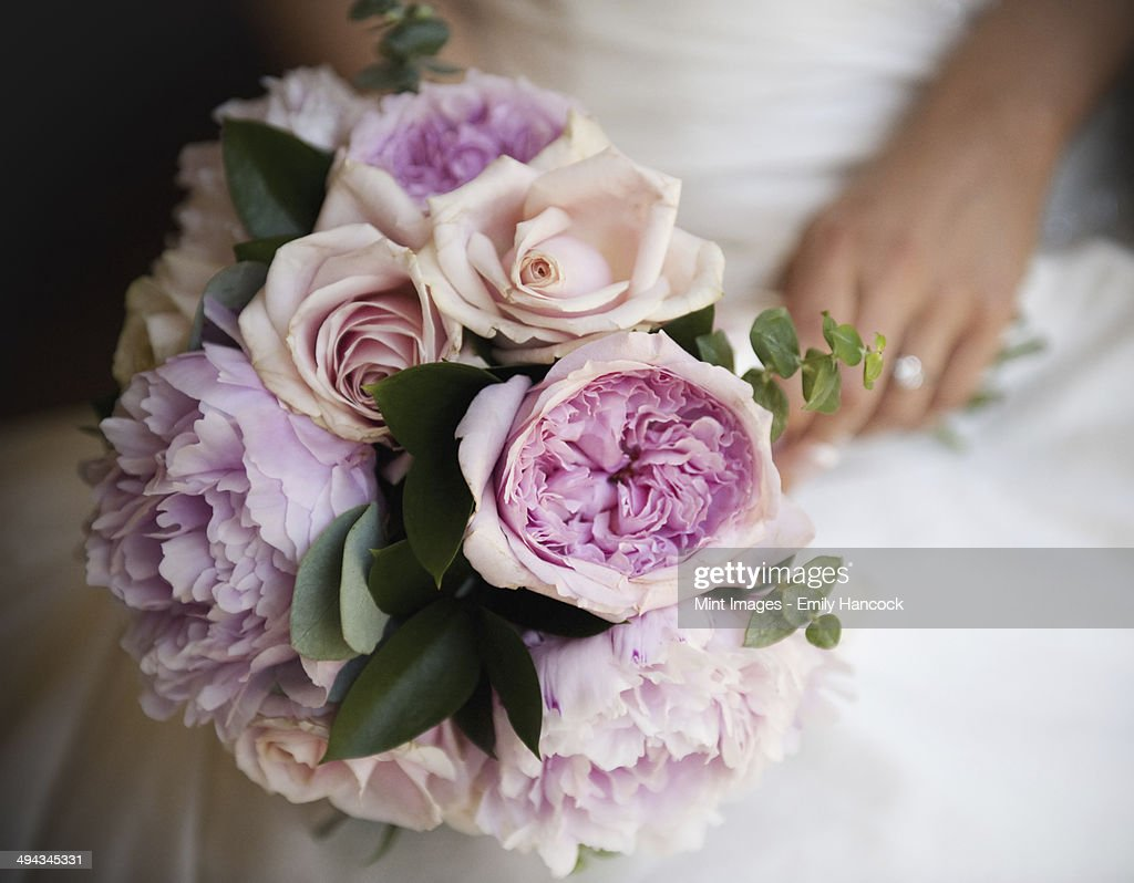 A woman, a bride holding a bridal bouquet of pastel coloured pale pink roses and peonies. : Stock Photo