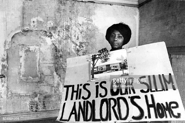 A woman a resident of the Cabrini Green housing projects holds up a sign that shows her building landlord's home Chicago Illinois 1960s The sign...