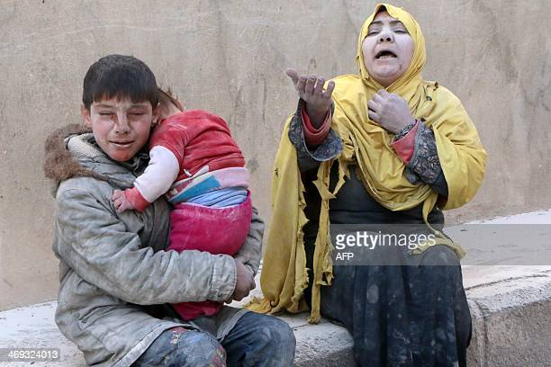 A woman a young boy and a baby covered with dust sit in a state of shock following a reported air strike attack by government forces on the Hanano...