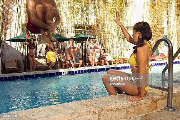 Woman about to be splashed by man doing cannon ball