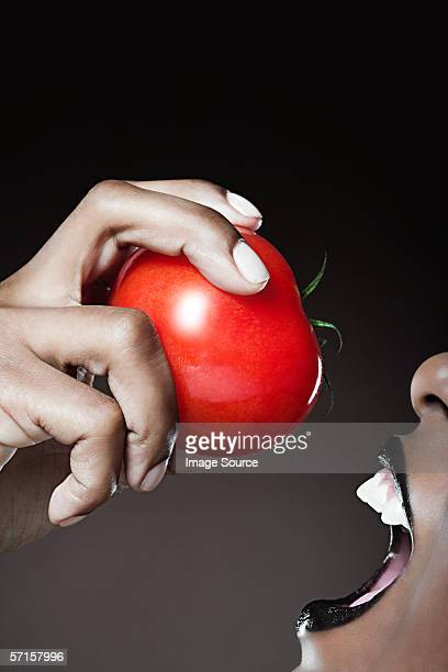 Woman about to bite into red apple