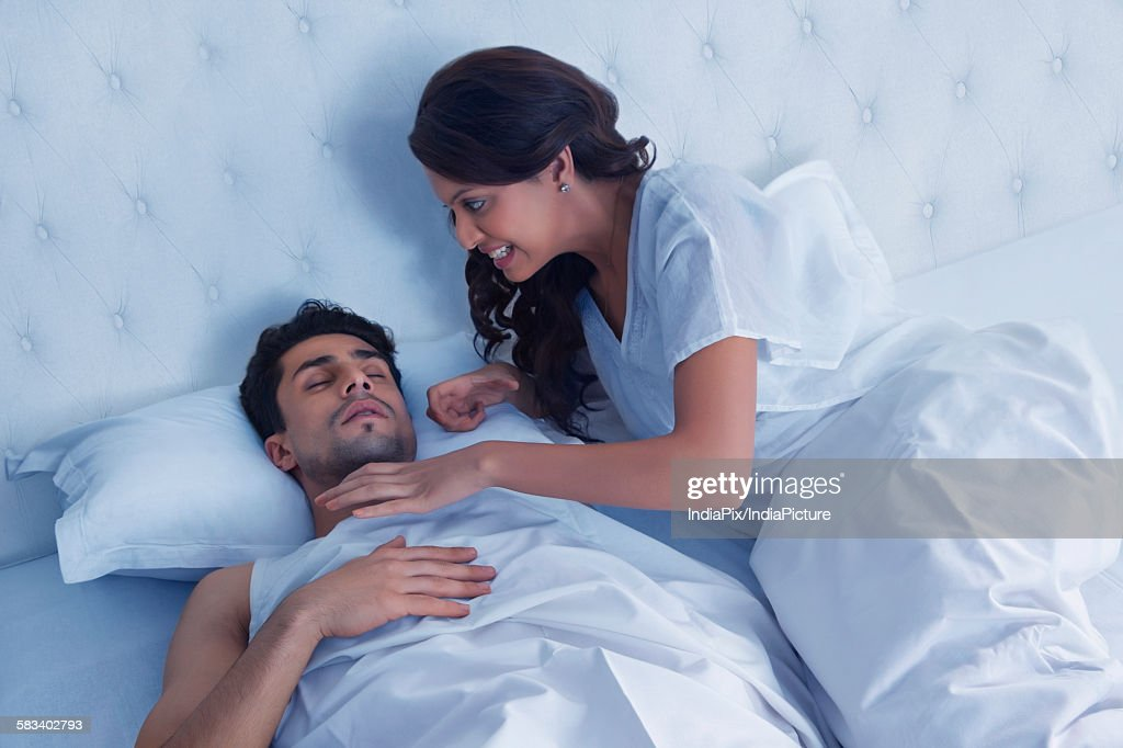 Woman about to choke snoring husband : Stock Photo