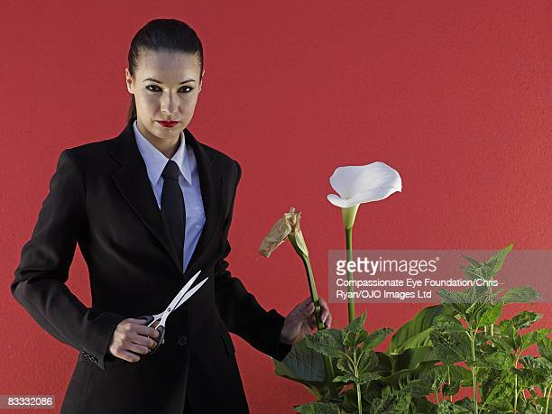 Woman about to cut dead flower