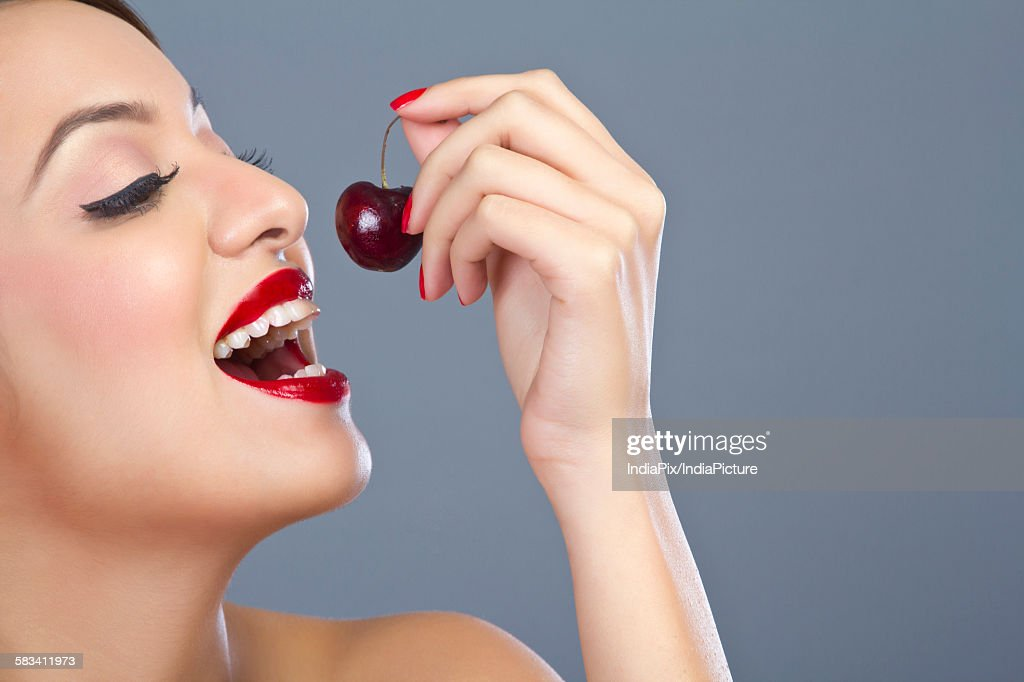 Woman about to eat a cherry : Stock Photo