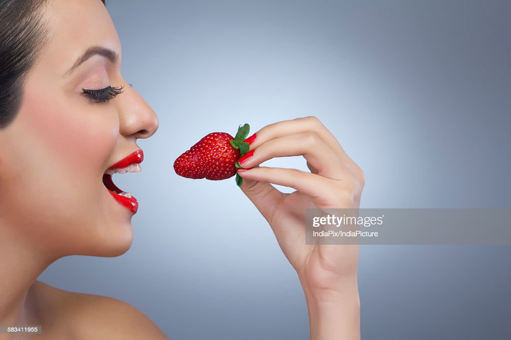 Woman about to eat a strawberry : Stock Photo