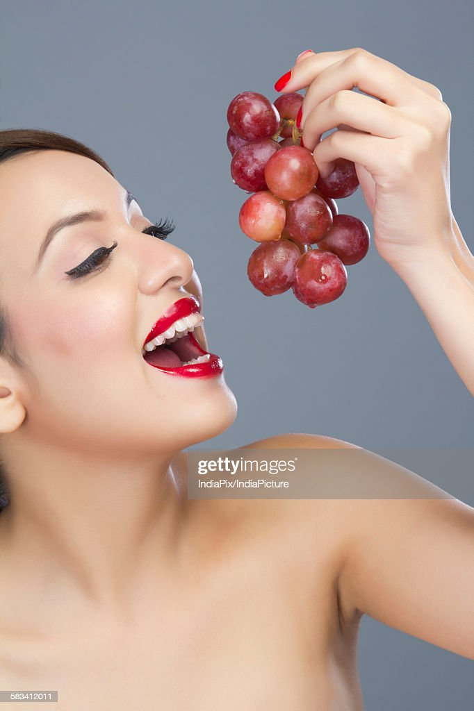 Woman about to eat grapes : Stock Photo