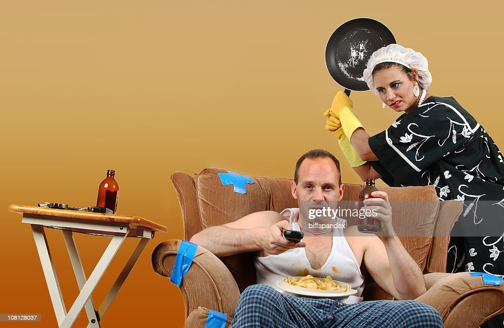 Woman About to Hit Oblivious Man with Frying Pan : Stock Photo
