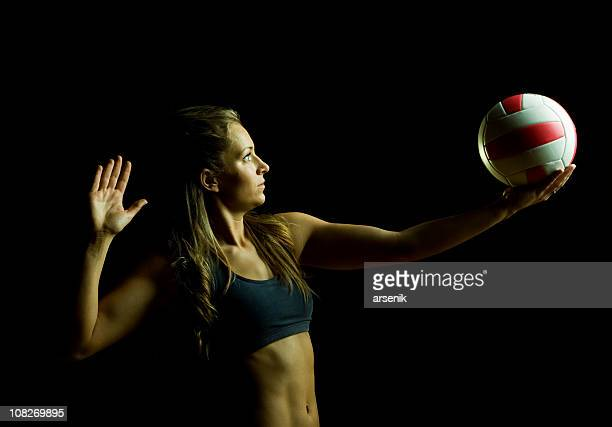 Woman About to Serve Volleyball, Isolated on Black