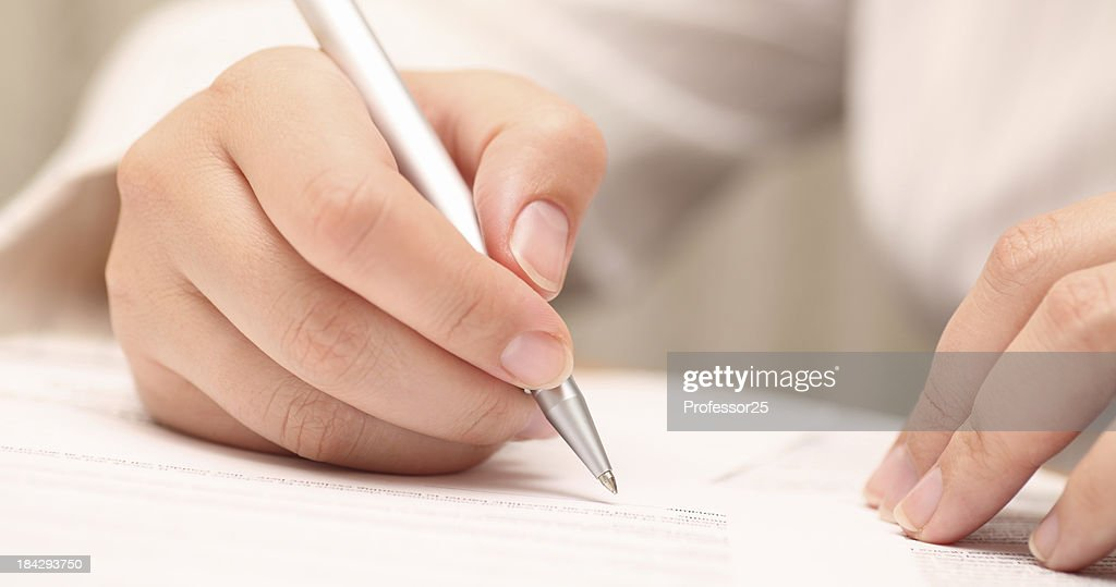 Woman about to sign a document with a silver pen. : Stock Photo