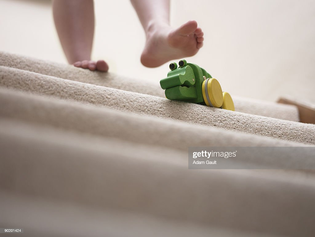 Woman about to slip on toy left on staircase : Stock Photo