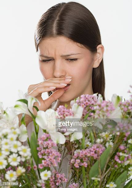 Woman about to sneeze and holding flowers