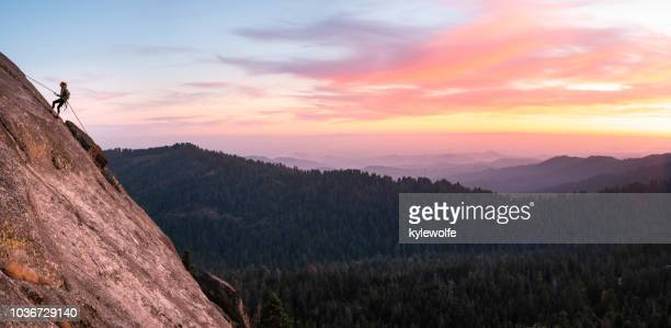 woman abseiling down a cliff at sunset, sequoia national park, california, united states - naturwunder stock-fotos und bilder