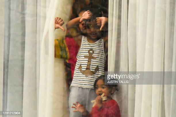 Woman accompanied by a boy and girl stand and gesture out of a window from inside the Radisson Blu hotel at Heathrow Airport in west London on...