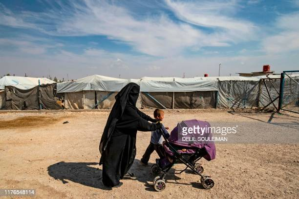 Woman accompanies children at the Kurdish-run al-Hol camp for the displaced where families of Islamic State foreign fighters are held, in the...