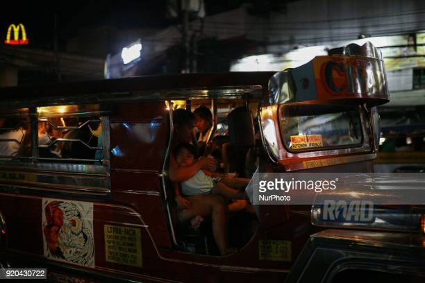 A woman acting as the jeepney driver's conductor holds her child inside a jeepney in Manila Philippines on Friday February 3 2018 The Jeepney has...