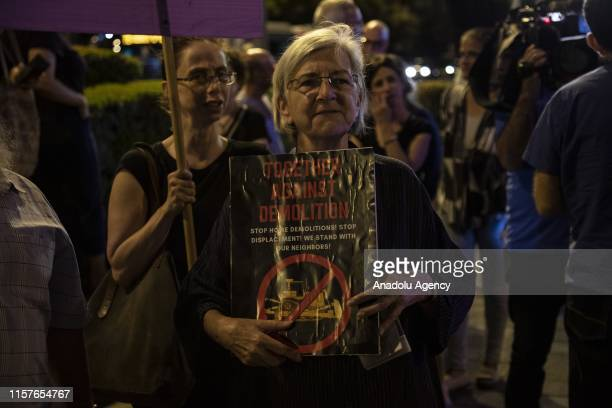 A woman activist holds placards as a group of Palestinian and Israeli activists gather to protest against Israels demolition policy aimed at razing...