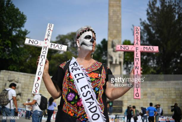 A woman activist raises crosses during a demonstration against the Government in demand of their missing relatives in Mexico City on May 10 2017...