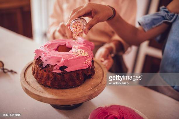 woman adding colorful sprinkles on cake icing - cake decoration stock pictures, royalty-free photos & images