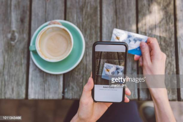 woman adding credit card into digital wallet - nfc stock pictures, royalty-free photos & images