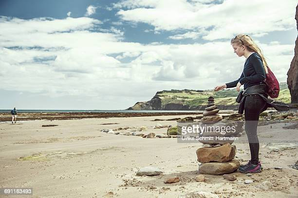 Woman adding pebble to cairn
