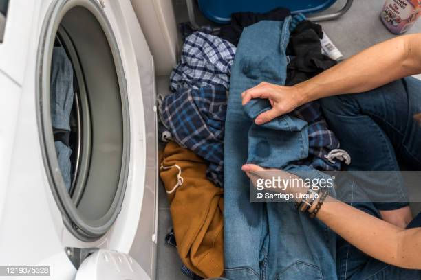 woman adding stain remover to clothes before washing them - trousers stock pictures, royalty-free photos & images