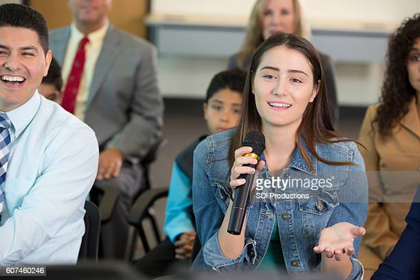 woman addresses a political candidate during town hall meeting - town hall meeting stock photos and pictures